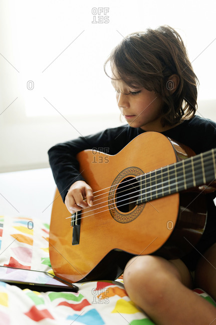 Boy sitting on bed using digital tablet for playing song on guitar