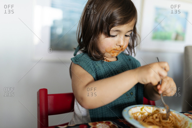 Portrait of little girl with smeared face eating pasta