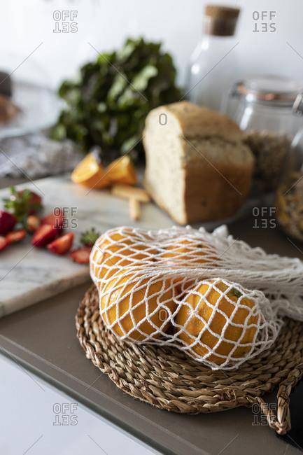 Oranges in net on kitchen counter