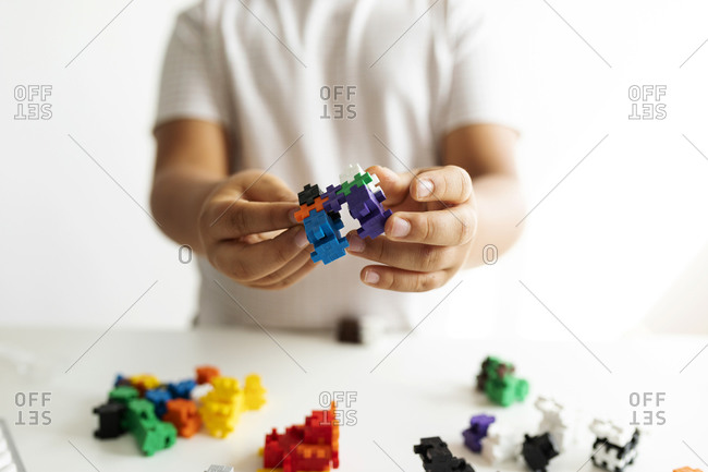 Children's hands holding building blocks- close-up