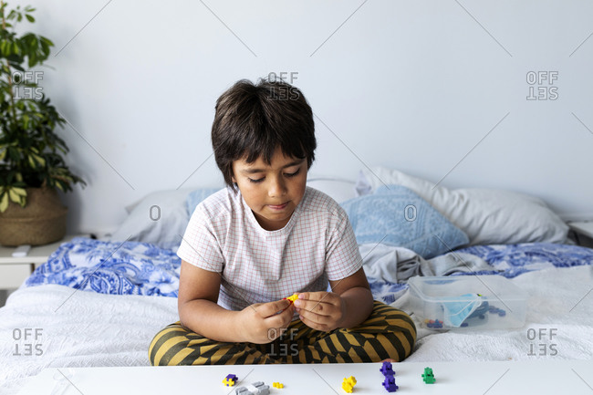 Boy sitting on bed playing with building blocks