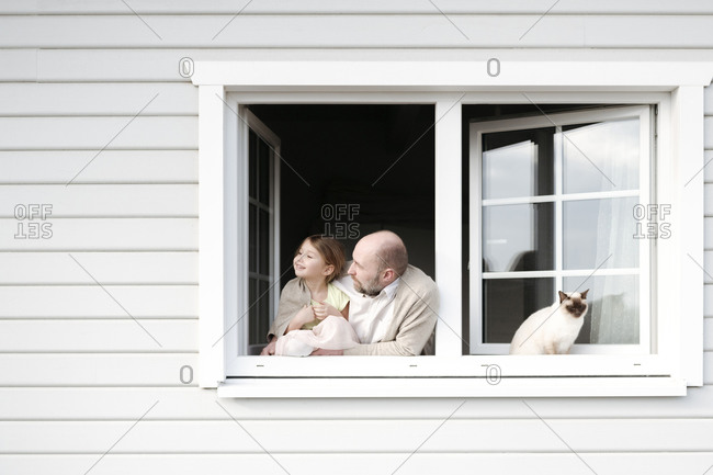 Mature man with smiling daughter and cat leaning out of window of his house