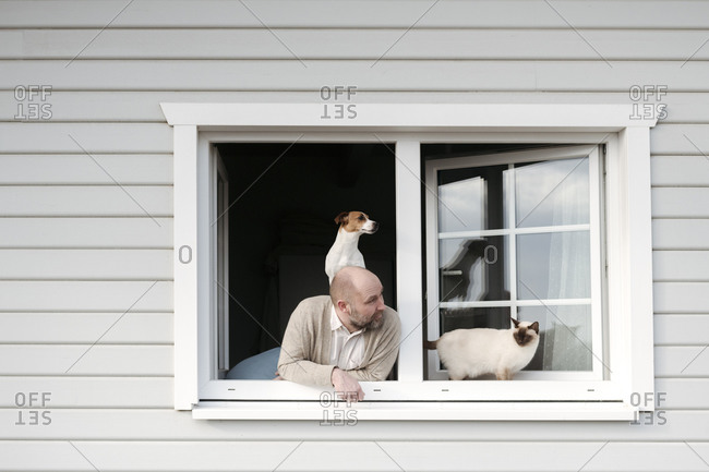 Mature man with cat and dog leaning out of window of his house