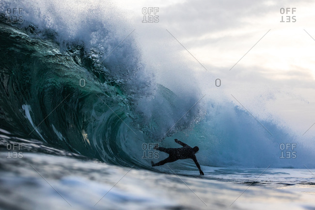Surfer falling from a cresting wave in the ocean