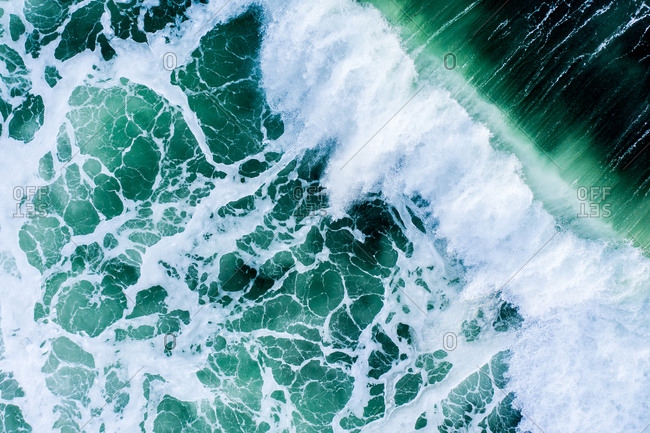 Overhead view of splashing turquoise waves in the ocean