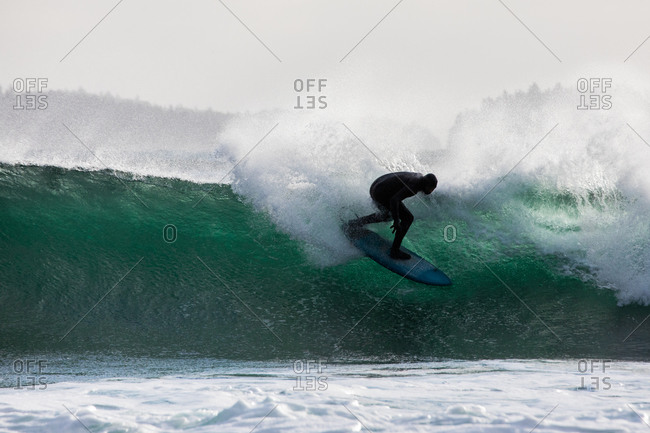 Surfer in a wetsuit riding a large wave in the ocean