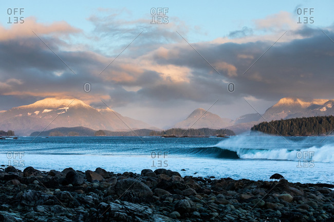 Waves cresting in the ocean as they roll into a rocky beach