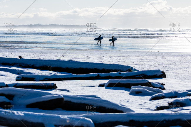 Two surfers walking on beach with surf boards