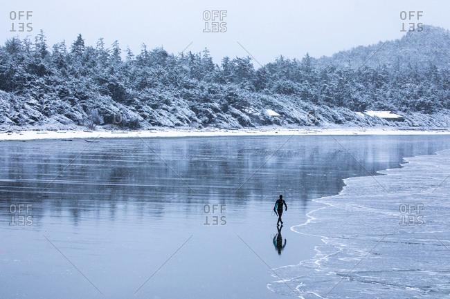 Man walking on beach with surf board in winter