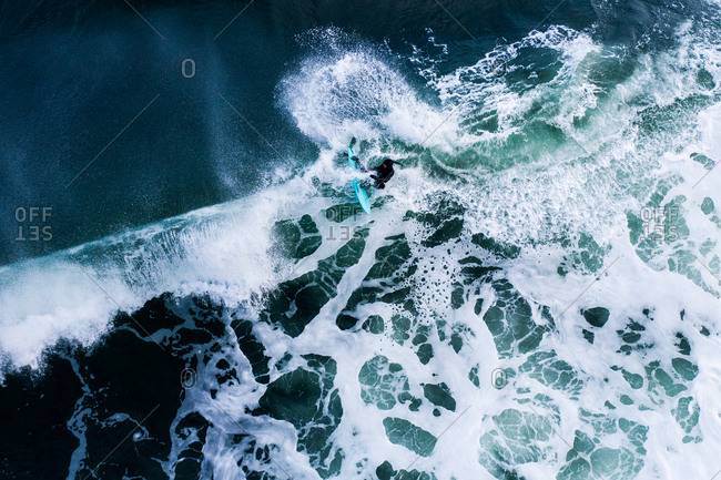 Overhead view of surfer riding splashing waves in the ocean