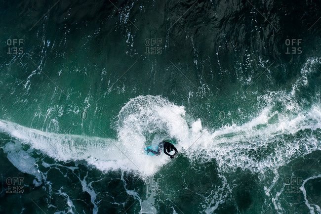 Overhead view of surfer riding turquoise waves in the ocean