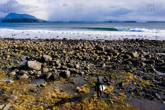 Man walking on rocky beach towards ocean with surf board