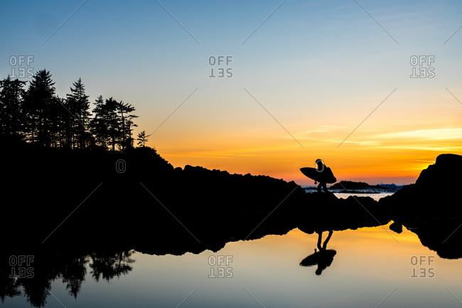 Man walking on rocky beach towards ocean with surf board