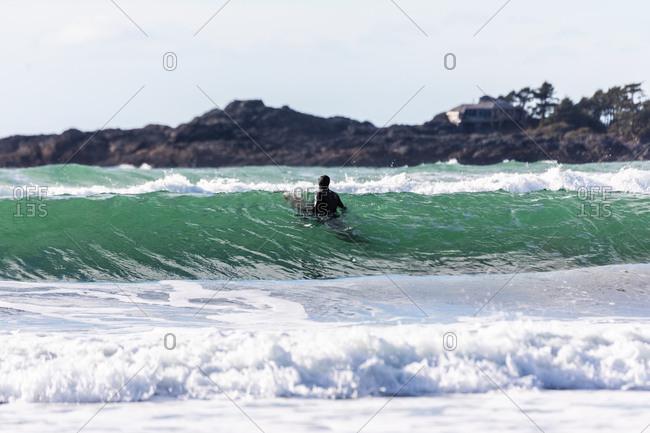 Surfer in a wetsuit on board in the ocean