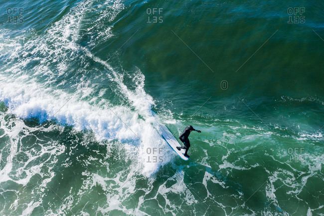 Bird's eye view of surfer riding turquoise waves in the ocean