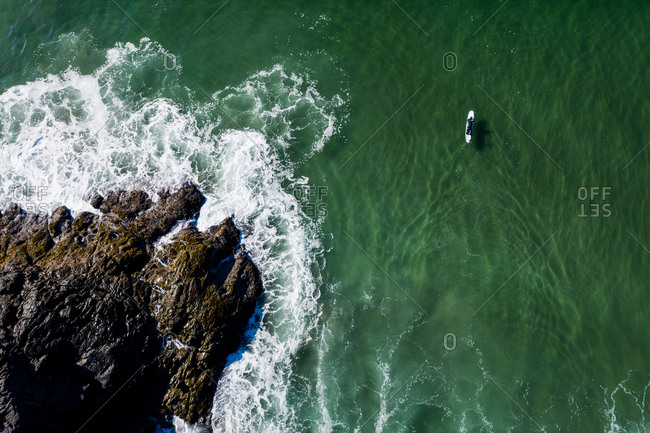 Aerial view over surfer on board in the ocean