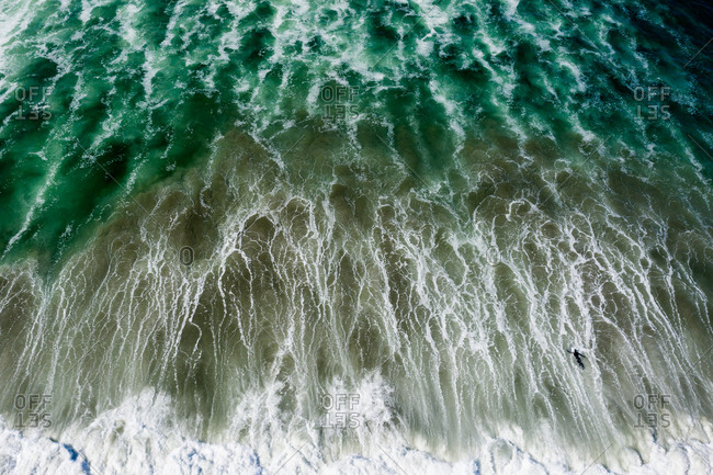 Aerial view over dramatic turquoise waves and surfer paddling on surfboard