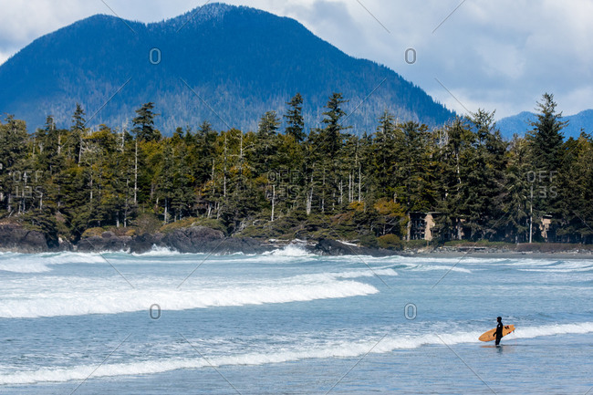 Surfer walking with board in the ocean