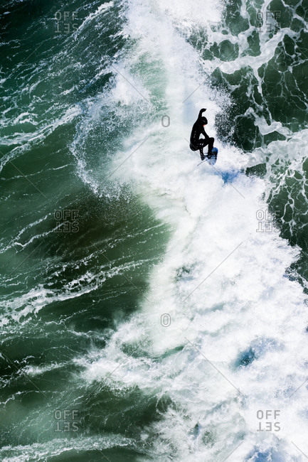 Aerial view of surfer riding foamy waves in the ocean