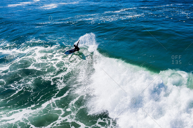 Bird's eye view of surfer riding blue waves in the ocean