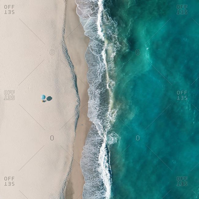 Aerial view of a lonely beach umbrella along the sea shore, Sant'Andrea Apostolo dello Ionio, Calabria, Italy.