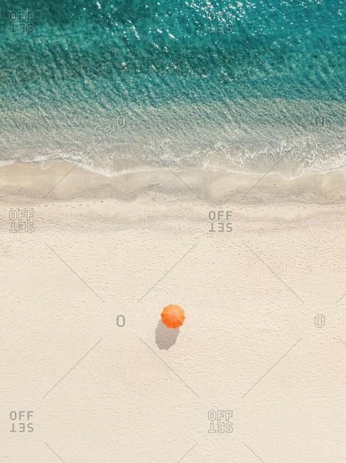 Aerial view of a lone orange parasol in a tranquil beach, Sant'Andrea Apostolo dello Ionio, Calabria, Italy.