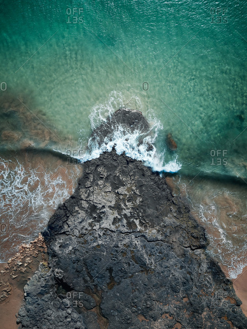 Aerial view of a big wave hitting a lava rock in an amazing sea with stunning colors, Playa del Pozo, Lanzarote, Spain.
