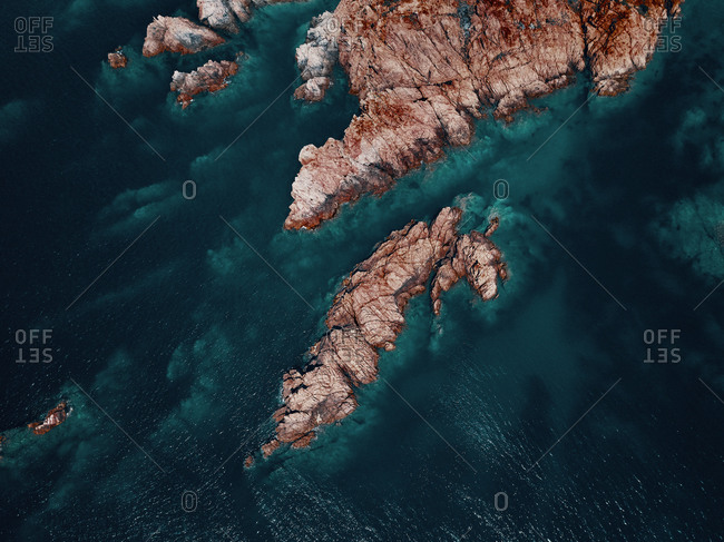 Aerial view of a reddish secluded reef diving in a transparent blue sea near Isola Rossa, Sardinia, Italy.
