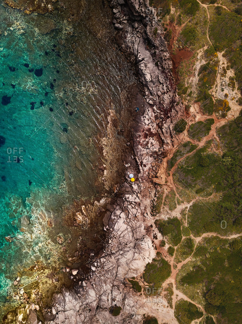 Aerial view of a secluded rocky beach in front of amazingly colored sea waters, Santa Maria La Palma, Sardinia, Italy.