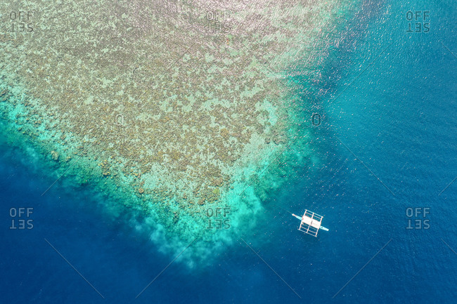 Aerial view of  Reef with Boat in front of CYC Beach, Coron, Palawan, Philippines.