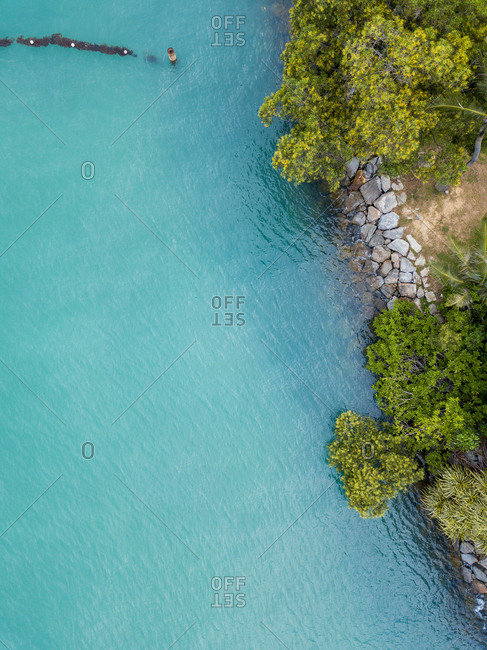 Aerial view of blue ocean, rocks, coastline and green trees on Sentosa Island, Islands of Singapore, Singapore.