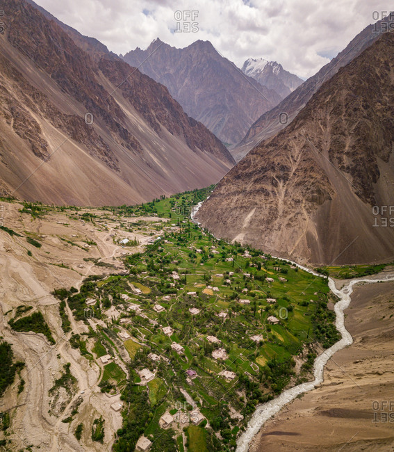 Aerial view of lush village with fields and trees next to a river surrounded by rocky desert mountains. Bardara, Bartang, Pamir, Tajikistan