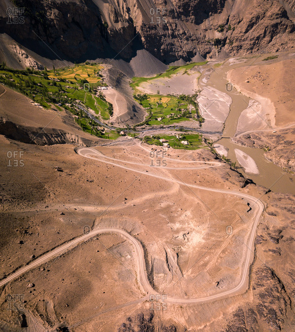 Aerial view of a winding dirt road leading to a lush village with fields and trees amidst a dry rocky desert. Bartang, Pamir, Tajikistan