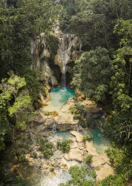 Aerial view of the famous tourist attraction Kuang Si Waterfalls, showing beautiful limestone basins nestled between lush trees. Luang Prabang, Laos