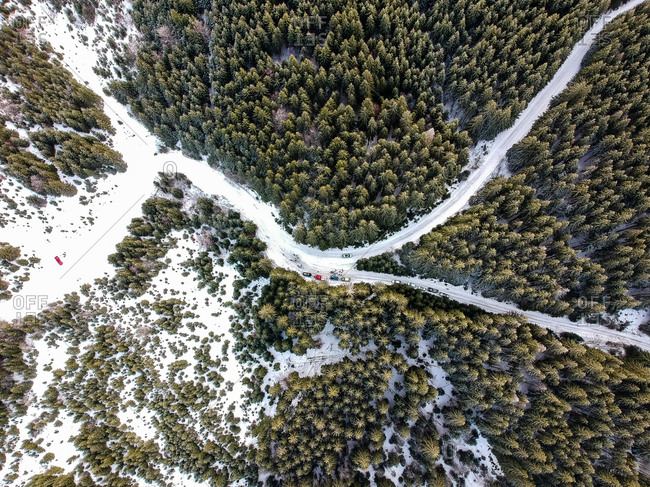 Aerial view of the official and emergency vehicles and some spectators at a check point of a winter rally near Comandau, Covasna, Romania