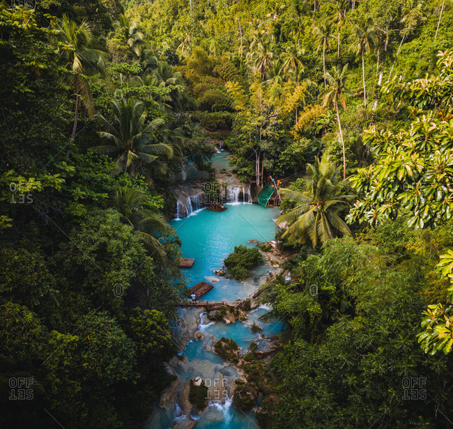 Aerial view of Cambugahay Falls surrounded by trees in Tigbawan, Lazi, Siquijor, Philippines