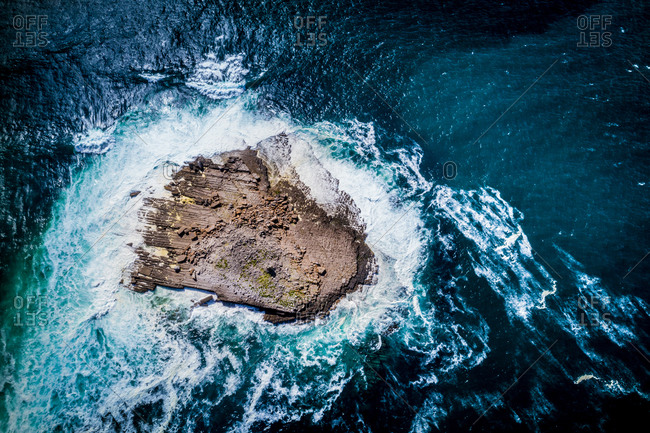 Aerial view of the rocky Crab Island splashed by big waves of the Atlantic Ocean, west coast of the Ireland, near Doolin.