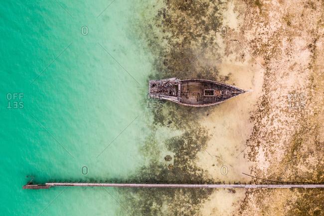 Aerial view of the abandoned old shipwreck at the coast of the Celebes Sea, Maratua Bohesilian near Borneo, Indonesia.