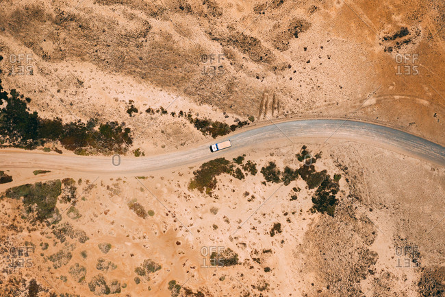 Aerial view of cargo truck driving on gravel road in arid desert climate, Majanicho, Fuerteventura island.