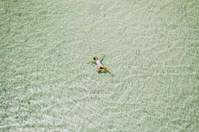 Aerial view of woman swimming in turquoise lagoon in Atlantic ocean near Fuerteventura island.