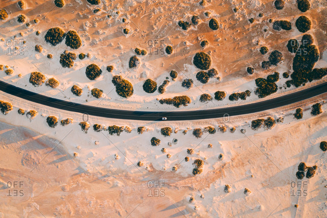 Aerial view of white car driving on curved road through desert in Fuerteventura island.