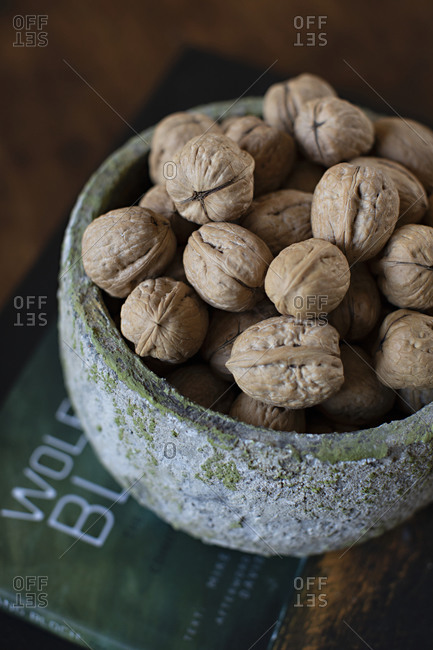 Whole walnuts in a green textured bowl