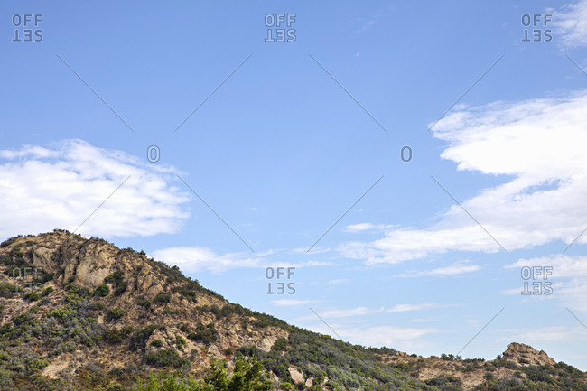 Rock formations under blue sky with clouds