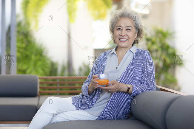 Happy senior Chinese woman relaxing in hotel room
