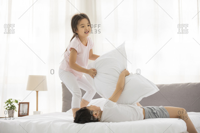 Happy Chinese sibling having fun in bedroom