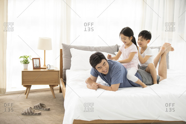 Happy young Chinese family having fun in bedroom