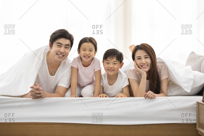 Happy young Chinese family relaxing in bed