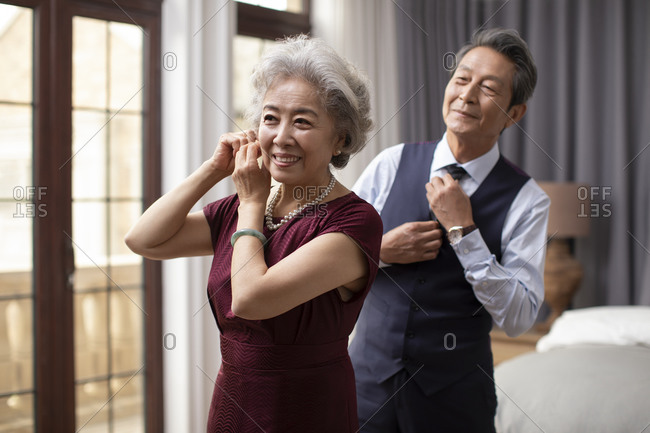 Happy senior Chinese couple getting dressed at home