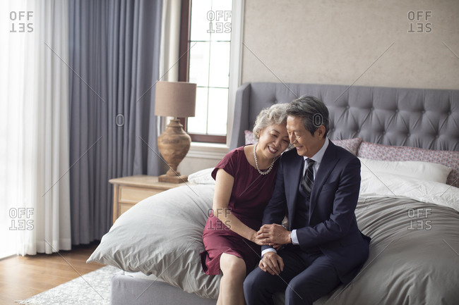 Happy senior Chinese couple enjoying their love in bedroom