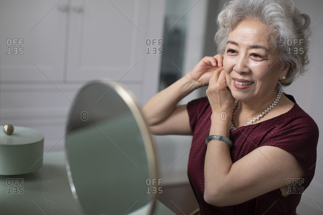 Happy senior Chinese woman wearing earring